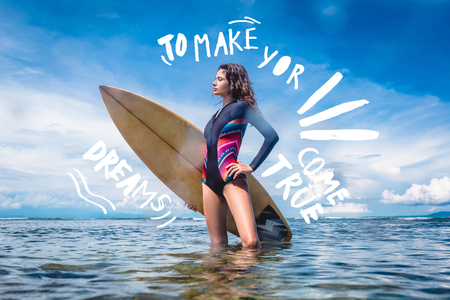 attractive sportswoman in wetsuit with surfing board standing in ocean at Nusa dua Beach, Bali, Indonesia. Inspiration - to make your dreams come true