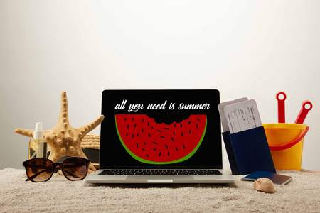 close up view of laptop  with all you need is summer lettering and watermelon illustration, sea star, sunglasses, passports with tickets and toy bucket on sand on grey background 写真素材