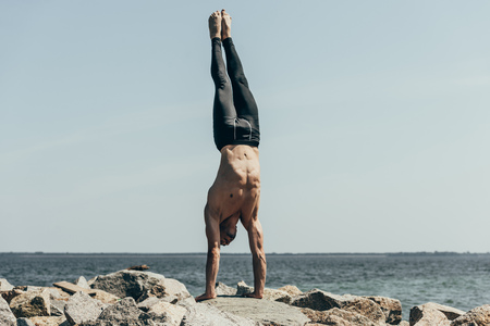 sporty shirtless man doing handstand (adho mukha vrksasana) on rocky seashore Фото со стока
