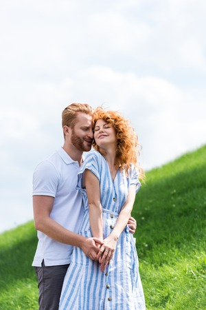 happy redhead man embracing girlfriend from behind on grassy hill Stock Photo
