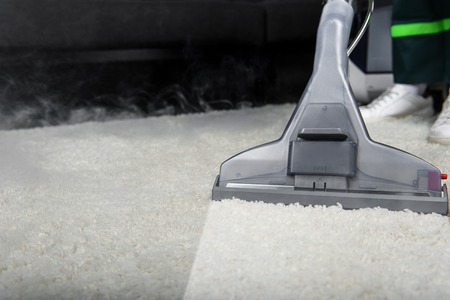 close-up view of person cleaning white carpet with professional vacuum cleaner