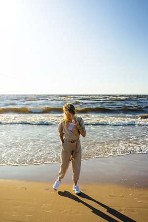 young woman in stylish clothing standing on seashore on summer day