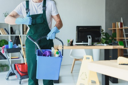 cropped shot of professional cleaner holding bucket with cleaning supplies and showing thumb up