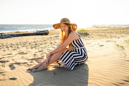 attractive young woman in straw hat resting on sandy beach in Riga, Latvia
