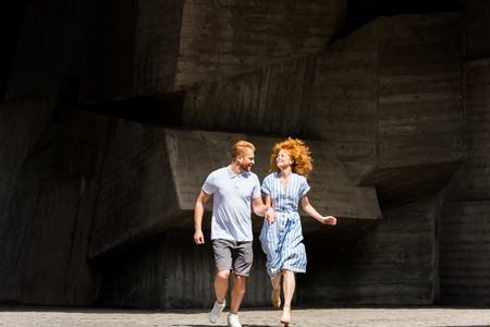 smiling redhead couple holding hands running at city street