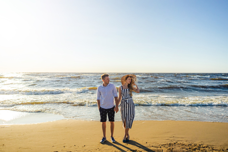 young couple in love holding hands on sandy beach in Riga, Latvia