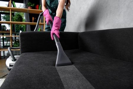 Vista parcial de la mujer con guantes de goma limpiando muebles con aspiradora