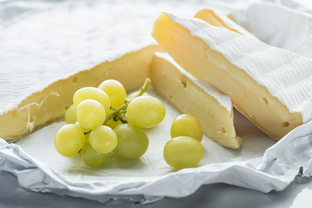 close up view of brie cheese and grape