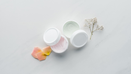 top view of bottles of cream, dried flowers and rose petals on white surface, beauty concept