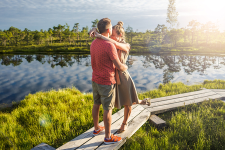 couple in love hugging each other on wooden bridge with green trees and river on background Foto de archivo - 106422178