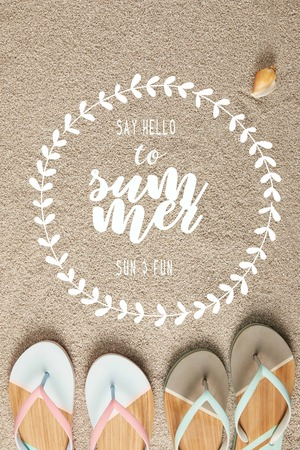 flat lay with summer flip flops and seashell on sand with say hello to summer lettering in floral frame