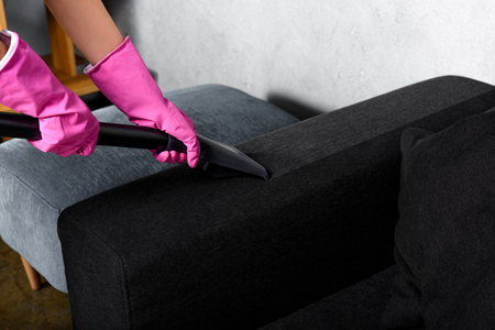 close-up partial view of person in rubber gloves cleaning sofa with vacuum cleaner Stok Fotoğraf