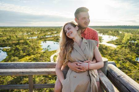 portrait of affectionate couple in love hugging on wooden bridge
