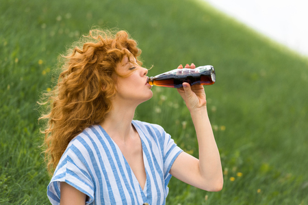 side view of beautiful redhead woman drinking soda outdoors 免版税图像
