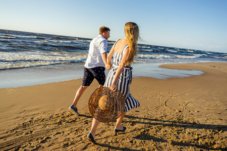 partial view of young couple in love holding hands and running on sandy beach in Riga, Latvia