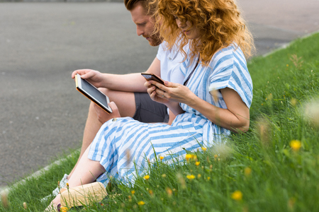 redhead woman using smartphone while her boyfriend sitting near with digital tablet on grass