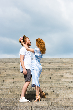 attractive redhead woman putting on own straw hat on boyfriends head on stairs