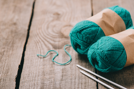 selective focus of wrapped green knitted yarn balls and knitted needles on wooden background