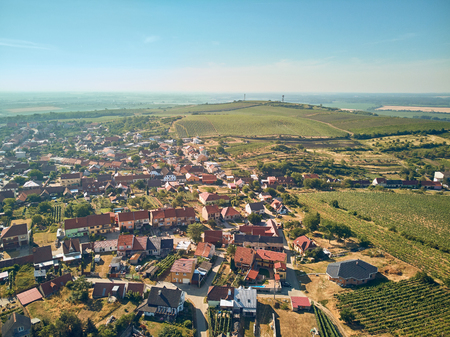 Aerial view of countryside with town and fields against blue sky, Czech Republic