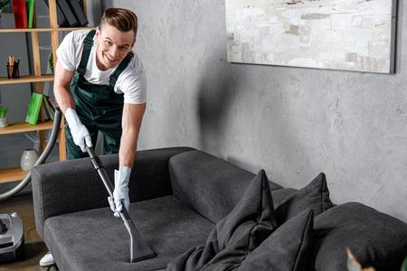 knappe jonge man in rubberen handschoenen meubels schoonmaken en glimlachen naar de camera Stockfoto