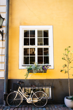 urban scene with bicycle parked near bright yellow building wall in Riga, Latvia