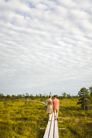 back view of couple in love walking on wooden bridge with green plants and blue sky on background Stock Photo