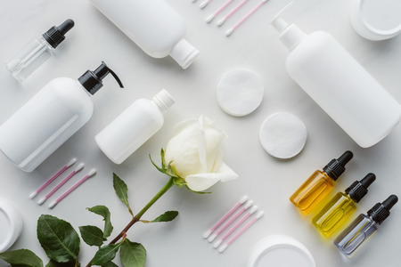 flat lay with bottles of cream, natural oils and rose on white surface, beauty concept Stock fotó