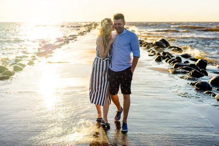 happy couple in love on seashore during sunset in Riga, Latvia