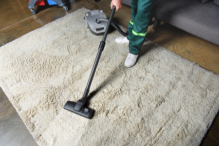 high angle view of man using vacuum cleaner and cleaning white carpet