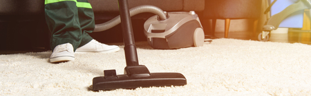 cropped shot of professional worker using vacuum cleaner and cleaning white carpet