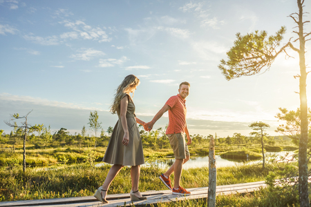 side view of couple holding hands while walking on wooden bridge with green plants and blue sky on background
