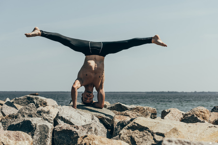 handsome shirtless man practicing yoga on rocks and performing tripod headstand in front of sea
