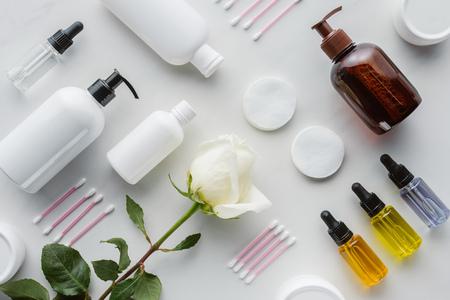 Vista superior de botellas de crema, almohadillas cosméticas y rosa sobre superficie blanca, concepto de belleza
