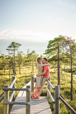 side view of affectionate couple hugging on wooden bridge with green plants and blue sky on background Foto de archivo - 106422724
