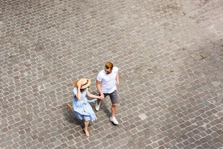 high angle view of woman in straw hat walking with redhead boyfriend at city street Фото со стока