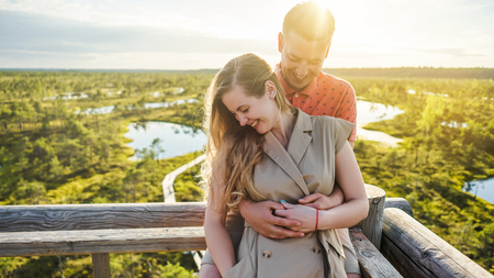 portrait of happy couple in love hugging on wooden bridge Stock Photo