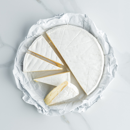 top view of camembert cheese on white marble tabletop