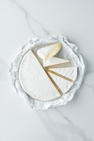 top view of brie cheese on white marble tabletop