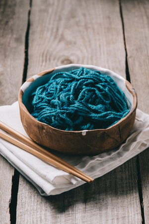selective focus of knitting needles, bowl with untangled knitting yarn and sackcloth on wooden background