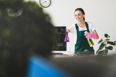 selective focus of smiling young woman with spray bottle and rag cleaning computer monitor in office