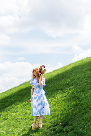 beautiful redhead woman holding straw hat on grassy hill