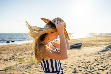 side view of attractive young woman in straw hat on sandy beach in Riga, Latvia Stock Photo