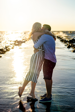 beautiful couple in love hugging and kissing on seashore during sunset in Riga, Latvia