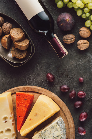 food composition with bottle of wine, grape, bread pieces and assorted cheese on dark surface 免版税图像