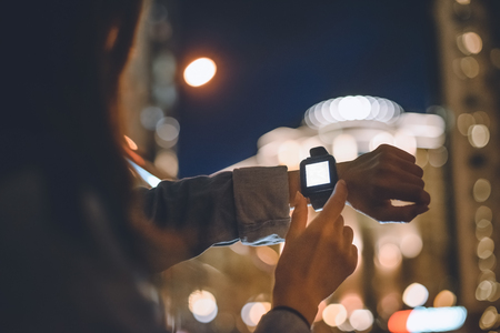 partial view of woman with smartwatch on wrist and night city lights on background