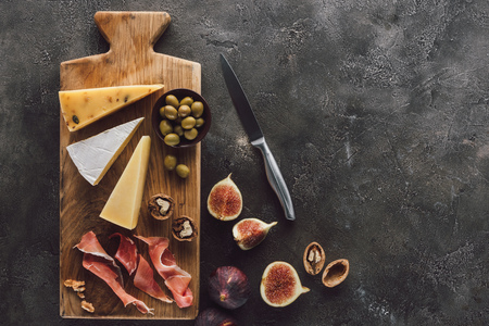 flat lay with assorted cheese, jamon and figs on dark surface