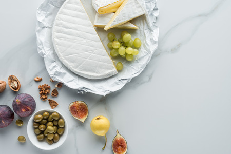 flat lay with olives, camembert cheese and fruits arranged on white marble surface