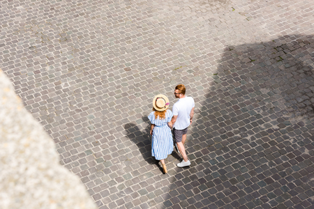 high angle view of redhead couple holding hands and walking at city street Stock Photo