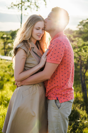 portrait of loving couple hugging with green plants on background