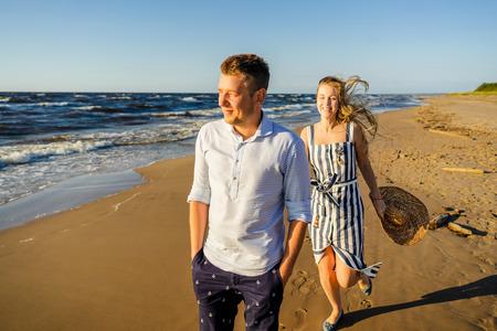 portrait of happy couple in love walking on sandy beach in Riga, Latvia Stock Photo